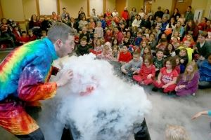 a scientist in a tie dye labcoat showing special effects with dry ice